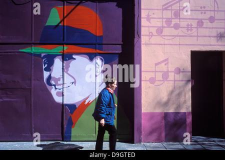 Eine Frau geht durch die Nachbarschaft der Abasto vor einem Plakat mit dem Bild von Carlos Gardel. - Stockfoto