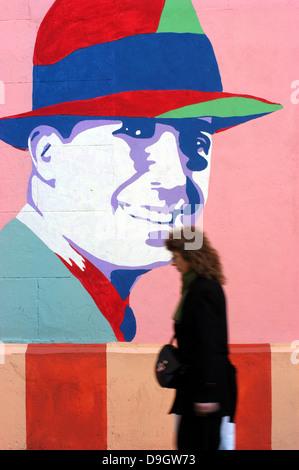 Eine Frau geht durch die Nachbarschaft der Abasto vor einem Plakat mit dem Bild von Carlos Gardel - Stockfoto