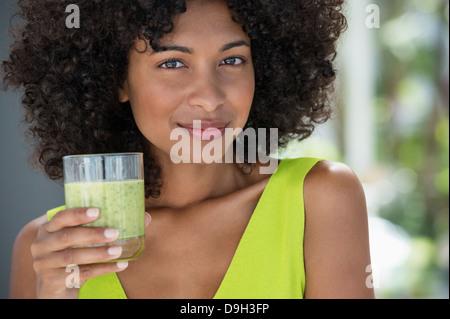 Porträt einer Frau mit einem Glas Kiwi-Saft - Stockfoto