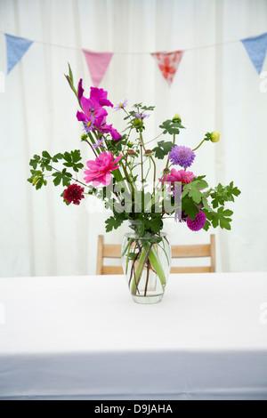 einfache Anordnung der Blumen in Glasvase auf Tisch im Festzelt mit Girlanden im Hintergrund für Land themed Hochzeit - Stockfoto