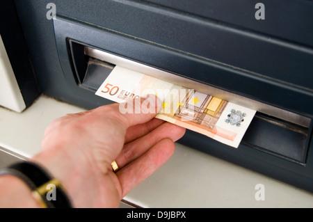 Hand nimmt 50 Euro Rechnung von bancomat Steckplatz - Stockfoto
