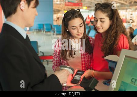 Zwei Mädchen im Teenageralter am Flughafen check-in Bereich - Stockfoto