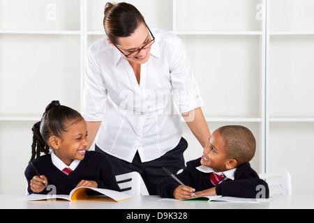 Volksschullehrer im Gespräch mit Schülern im Klassenzimmer