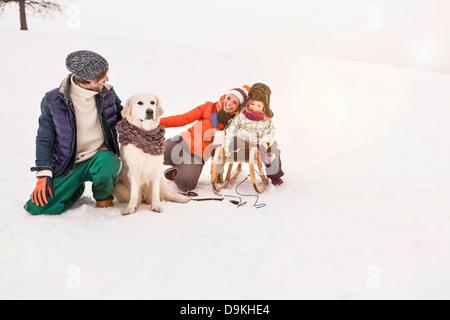 Eltern mit Tochter auf Schlitten im Schnee - Stockfoto