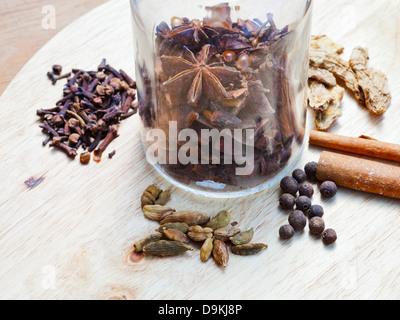 Glasflasche mit set Gewürze für Glühwein auf Holztisch - Stockfoto