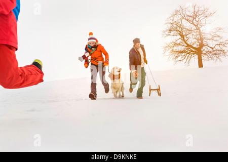 Paar laufen im Schnee, Man zieht Rodeln - Stockfoto