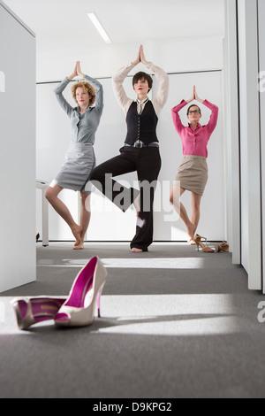 Drei Frauen, die Yoga im Büro - Stockfoto
