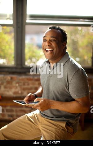 Mann posiert mit charismatischen Lächeln halten digital-Tablette - Stockfoto
