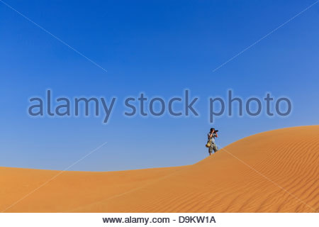 Mann Fotografieren in Sanddünen in der Wüste, Dubai, Vereinigte Arabische Emirate - Stockfoto