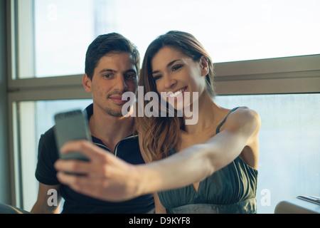 Junges Paar fotografieren sich auf Smartphone in Flughafen - Stockfoto