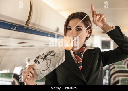 Luft Stewardess Sicherheit Demonstration am Flugzeug durchführen - Stockfoto