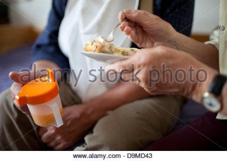 Ältere Frau Fütterung Essen zu ihrem kranken Mann - Stockfoto