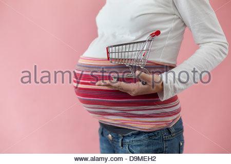 Schwangere Frau hält einen Einkaufswagen - Stockfoto
