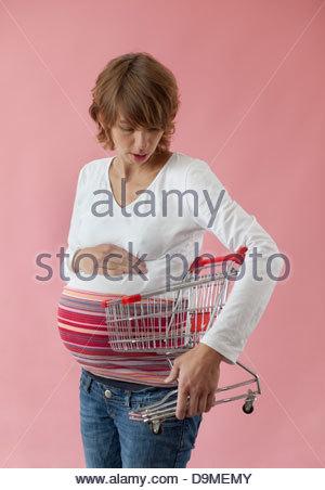 Schwangere Frau, die einen Einkaufswagen - Stockfoto