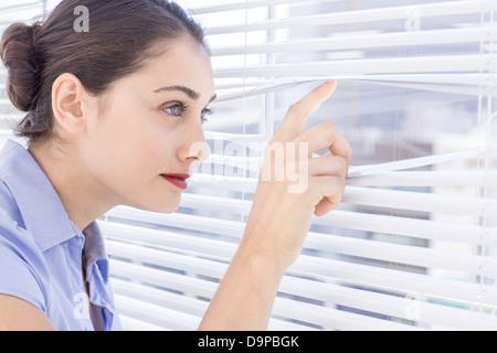 Hübsche Geschäftsfrau spähen durch eine Jalousie - Stockfoto
