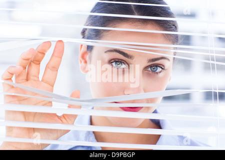 Hocherfreut Geschäftsfrau spähen durch eine Jalousie - Stockfoto
