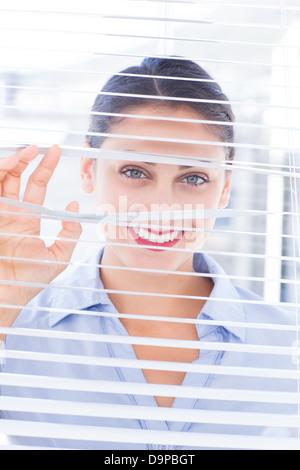 Fröhlich lächelnd durch Jalousie Geschäftsfrau - Stockfoto
