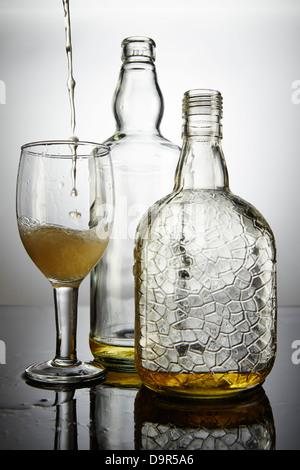 Champagner in ein Glas Wein neben Weinflaschen - Stockfoto