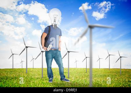 Student mit einer Glühbirne Kopf mitten in Wind-Turbine-Feld - Stockfoto