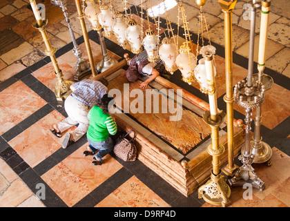 Israel, Jerusalem Altstadt, Kirche des Heiligen Grabes, Stein der Salbung, Leib Christi gewickelt Anbeter im Gebet - Stockfoto