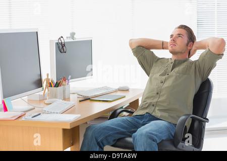 Schöner Designer wieder an seinem Schreibtisch gelehnt - Stockfoto