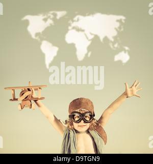 Glückliches Kind mit Spielzeugflugzeug gegen blauen Himmelshintergrund spielen. - Stockfoto