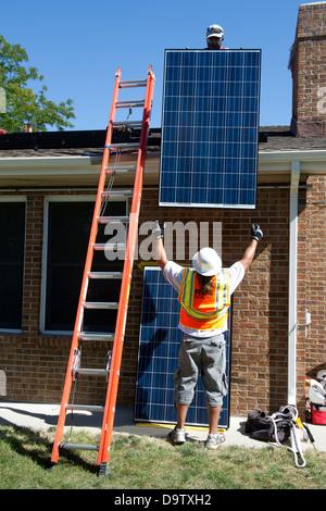 Bauarbeiter installieren Photovoltaik-Solarstromanlage auf dem Dach eines Hauses 10. September 2012 in Englewood, - Stockfoto