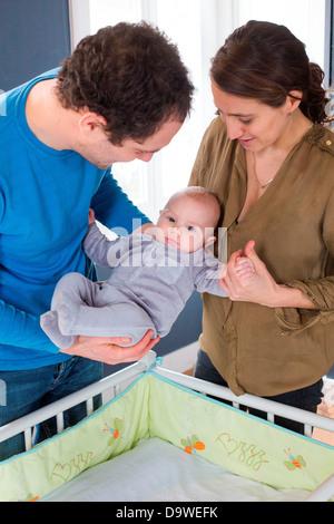 Mutter und Vater setzen ihre 5 Monate altes Baby Boy ins Bett - Stockfoto