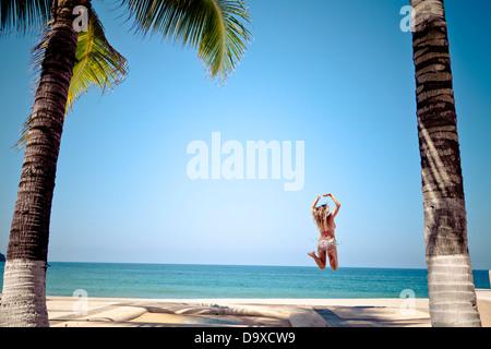Frau im Bikini am Strand springen - Stockfoto