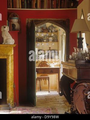 Roten Speisesaal mit gotischen gewölbte Tür mit Blick durch, Tisch und Stuhl im Cottage Landhausküche Kiefer - Stockfoto