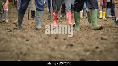 Glastonbury, UK. 28. Juni 2013. GLASTONBURY Musikfestival Festival Besucher tragen Gummistiefel wegen der klebrigen - Stockfoto