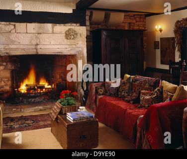 roten wurf auf sofa mit kissen neben kamin mit offenem kamin im wohnzimmer gem tlich land mit. Black Bedroom Furniture Sets. Home Design Ideas