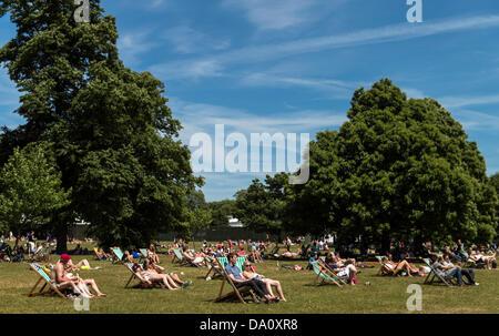 Menschen, die ein Sonnenbad im Hyde Park London UK am Sonntag 30. Juni Sommer 2013 - Stockfoto