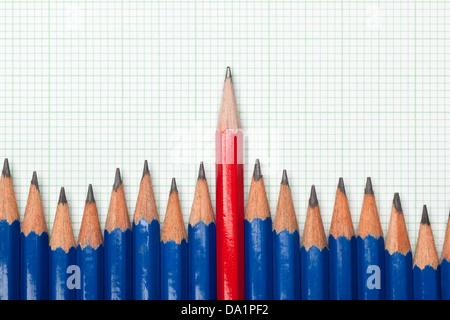 Rotstift stehend aus einer Reihe von blauen Bleistift auf einem Blatt Zeichenpapier mit Maßeinteilung - Stockfoto