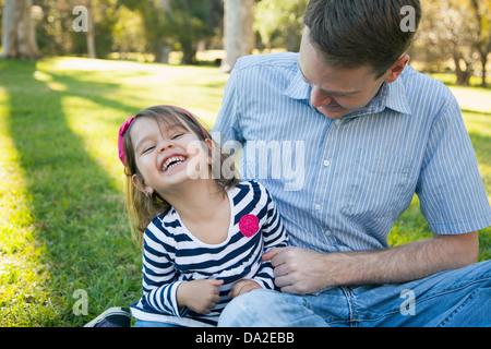 USA, California, Irvine, Vater kitzeln seine Tochter (4-5) am sonnigen Tag im park - Stockfoto