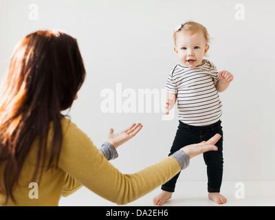 Mutter, die Hände in Richtung ihrer Tochter (12-17 Monate) - Stockfoto