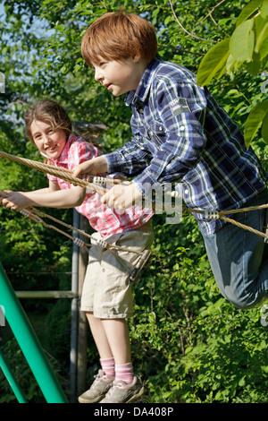 junges Mädchen und Jungen gemeinsam auf Schaukel - Stockfoto