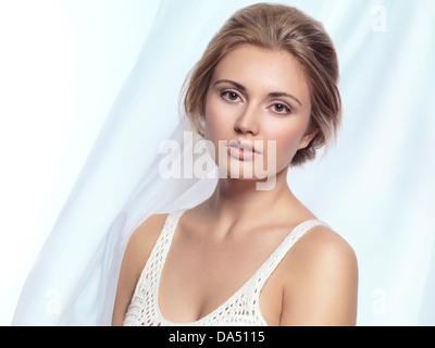 Porträt einer schönen jungen Frau auf hellblauen flowy Stoff Hintergrund - Stockfoto