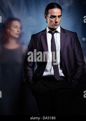 Emotionales Porträt eines jungen Mannes mit traurigen, nachdenklichen Ausdruck und eine junge Frau hinter einem - Stockfoto