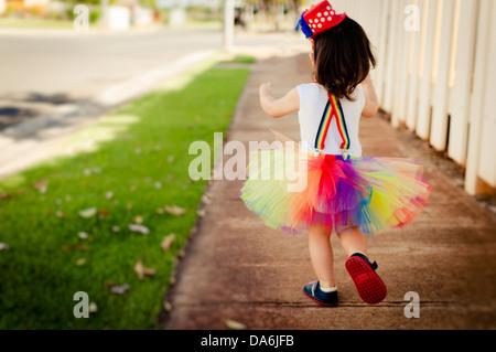 Kleine Asiatin in einem Clown-Outfit und mit einem Lolly Pop spielen - Stockfoto