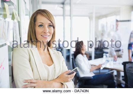 Geschäftsfrau mit Handy stehen im Büro - Stockfoto
