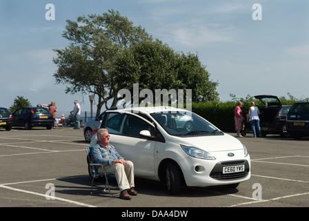 Senior woman, Oap Sonnenbaden im Stuhl Parkplatz hochklappen. HOMER SYKES - Stockfoto