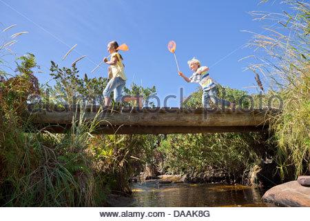 Fröhlicher Junge und Mädchen mit Fischernetzen läuft auf Fußgängerbrücke über Bach - Stockfoto