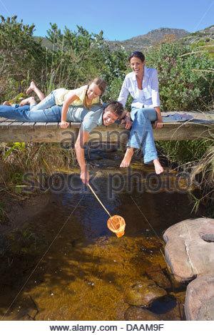 Familie Verlegung auf Steg und Dippen Fischernetz im stream - Stockfoto