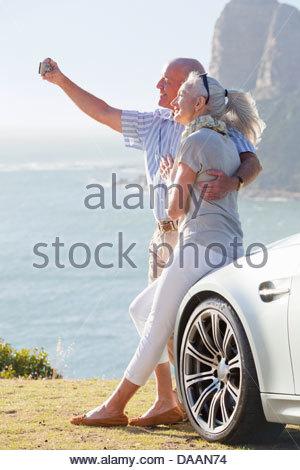 Paar an Auto gelehnt und Selbstporträt mit Kamera in der Nähe von Meer - Stockfoto