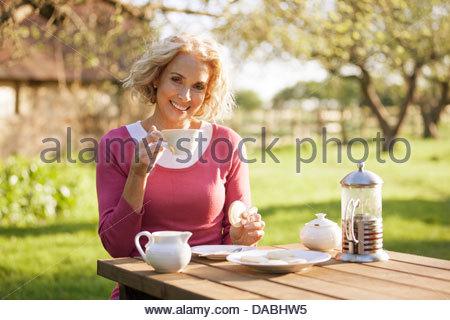Eine reife Frau mit Kaffee und Gebäck in einem Garten - Stockfoto