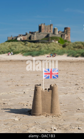 Union Jack-Flagge in eine Sandburg am Strand vor Bamburgh Castle. Northumberland, England - Stockfoto