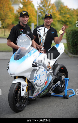 Konstruktor Thomas Schuricht (L) und seine Rennfahrer Matthias Himmelmann stehen neben das Elektromotorrad Münch - Stockfoto