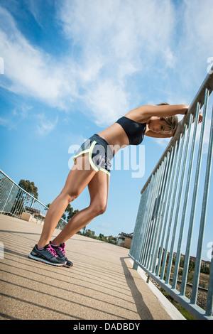 Weibliche Läufer stützte sich auf Geländer Stockfoto