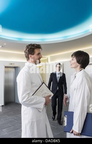 Mann und Frau tragen Laborkittel, Gespräch in der Lobby, tragen Geschäftskleidung Mann nähert sich - Stockfoto